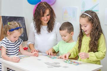 Wall Mural - Teacher plays with children in kindergarten.