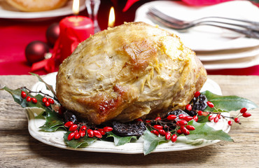 Baked pork with dried plums on christmas table