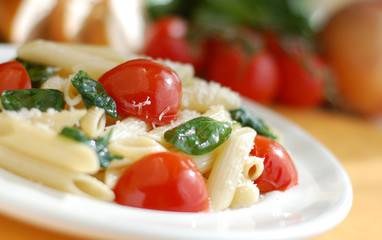 Plate of penne with tomatoes and spinach.