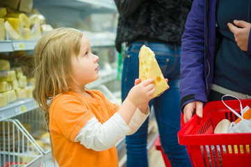 Adorable girl select cheese with mother in supermarket