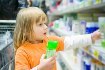 Adorable girl select shampoo bottles in supermarket