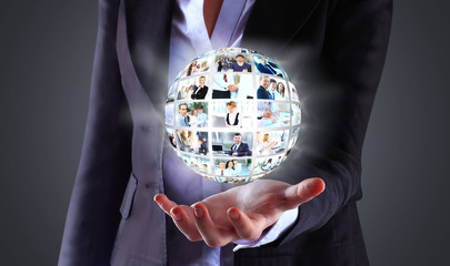 Business woman holding a ball of people on a dark