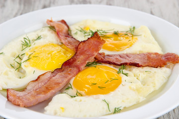 Scrambled eggs and bacon on plate on wooden table