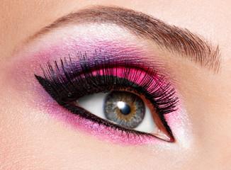 female eye with  beautiful fashion bright pink makeup