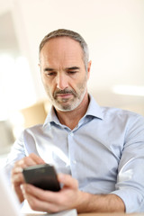 Senior businessman in office using smartphone