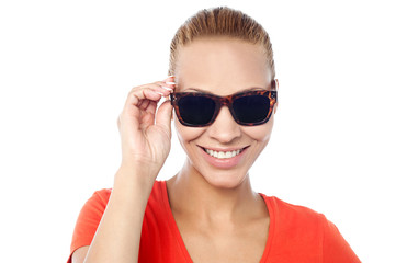 Trendy woman adjusting her sunglasses