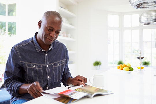African American Man Reading Magazine At Home