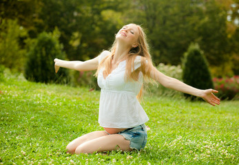 happy pregnant woman on the soft grass