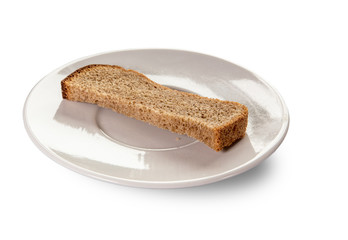 A dry piece of bread on a white saucer