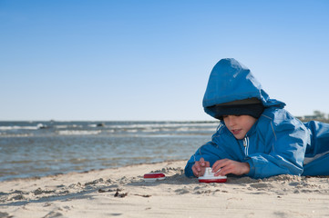 Little boy on the beach plays with little toy ships in autumn