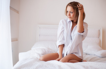 Portrait of a beautiful young woman in bed in the early morning
