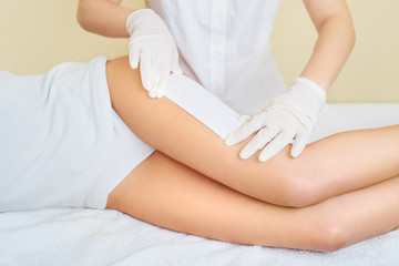 Young women waxing legs