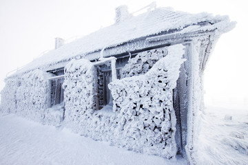Snow and ice covered hut in the mountains