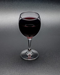 Glass of red wine on black background.