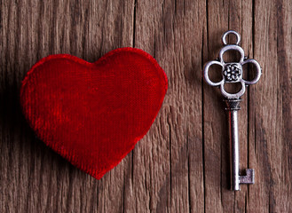 vintage key and red heart on wooden background