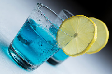 Glasses with blue cocktail and slices of lemon