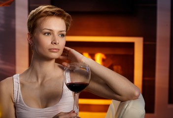 Daydreaming woman with glass of wine