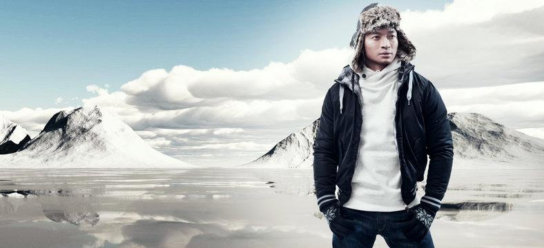 Asian winter fashion man in snow mountain landscape. Wearing bla