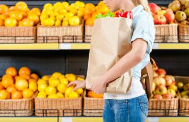 Choosing lemons girl hands bag with fresh vegetables in the shop