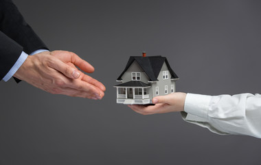 Close up of hands giving home model to other hands