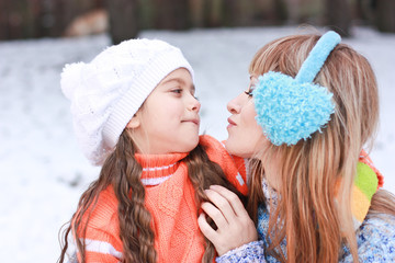 Mom and daughter in knitted sweaters look  in the winter