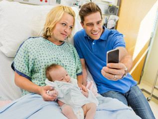Man With Woman And Babygirl Taking Selfportrait Through Mobile P