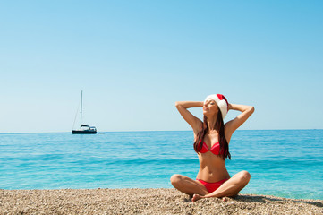Girl on the beach in a Christmas hat.
