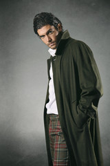 Male fashion model in green coat and texture backdrop
