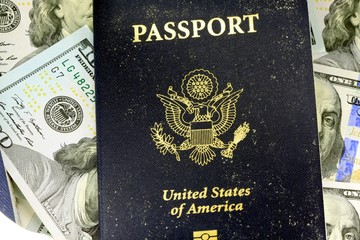United States travel passport with one hundred dollar bills
