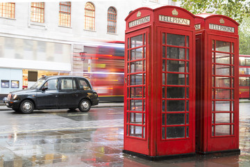 Red Phone cabines in London and vintage taxi.Rainy day.