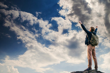 Man with victory gesture on the top of mountain