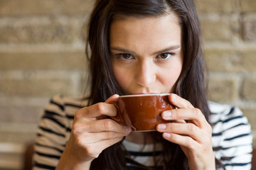 Closeup Of Woman Drinking Coffee At Cafe