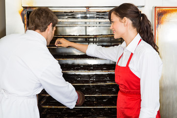 Workers Drying Meat In Oven At Butcher's Shop