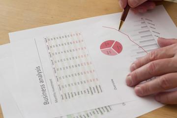 senior businessman holding a pen, analyzing charts