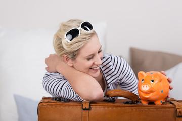 lachende frau mit koffer und sparschwein