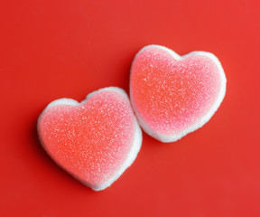 Sugar hearts on red background