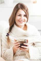 portrait of smiling woman sitting on sofa and holding tea cup