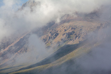 Fototapete - Clouds coverig rocks in mountains of Tien Shan
