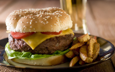 Closeup of a burger with fries and a cold beer.