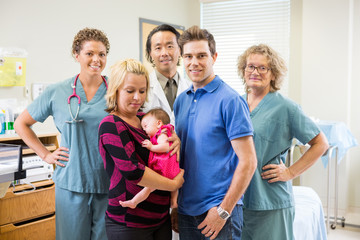 Medical Team With Newborn Baby Girl And Parents In Hospital