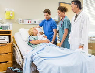 Medical Team And Man Looking At Mother With Babygirl