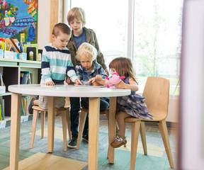 Children Using Digital Tablet In Library
