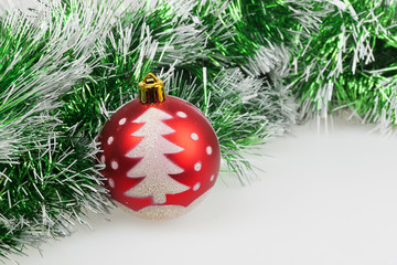red Christmas ball with painted Christmas tree and green garland