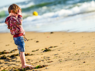 One young cute child standing in front of the ocean