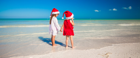 Little cute girls in Christmas hats on the exotic beach