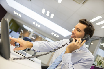 Portrait of smiling businessman at phone in office
