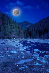 river  rocky shore near the mountain in moonlight