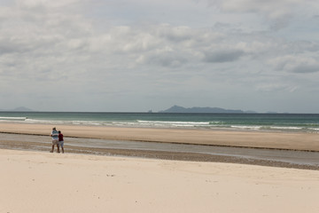 retired couple walking on Pakiri Beach