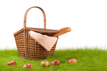 Picnic basket with long loaf and apples on the grass.