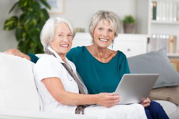 zwei seniorinnen arbeiten am laptop